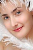 Nahaufnahmeportraitmädchen mit weißer Straußfeder Stockfotos
