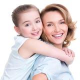 Nahaufnahmeporträt der glücklichen Mutter und der jungen Tochter Stockbild