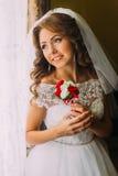 Nahaufnahmeporträt der lächelnden schönen Braut im Hochzeitskleid, das einen netten Blumenstrauß mit den roten und weißen Rosen h Lizenzfreies Stockfoto