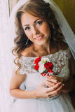 Nahaufnahmeporträt der schönen Braut im Hochzeitskleid, das einen netten Blumenstrauß mit den roten und weißen Rosen hält Stockfoto