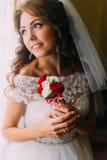 Nahaufnahmeporträt der schönen Braut im Hochzeitskleid, das einen netten Blumenstrauß mit den roten und weißen Rosen träumen sie  Stockfotografie