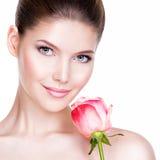 Nahaufnahmeporträt der schönen jungen Frau mit Blume nahe Gesicht Stockfotografie