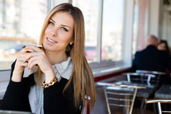 Nahaufnahmeporträt der trinkenden schönen netten blonden jungen Geschäftsfrau des Kaffees oder des Tees mit grünen Augen Lizenzfreies Stockfoto