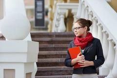 Nahaufnahmeporträt des recht jungen Studentenmädchens, das Übungsbücher und -ordner hält Lizenzfreies Stockbild
