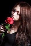 Nahaufnahmeporträt einer blassen schönen jungen Frau mit einer roten Rose Stockfotos