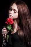 Nahaufnahmeporträt einer blassen schönen jungen Frau mit einer roten Rose Lizenzfreies Stockbild