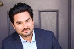 Nahaufnahmeporträt eines Geschäftsmannes gegen Backsteinmauerhintergrund Stockfotografie