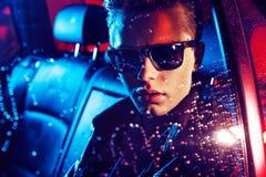 Nahaufnahmeporträt eines jungen Kerls, der im Auto stillsteht Lizenzfreie Stockfotos