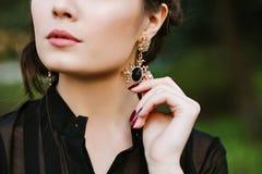 Nahaufnahmeporträt eines Mädchen Brunette Eine junge Frau berührt einen Ohrring mit Edelsteinen Goldohrring mit Schwarzem Lizenzfreies Stockfoto