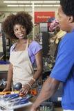 Nahaufnahmeporträt eines weiblichen Ladenangestellters des Afroamerikaners, der am Kassenscanneneinzelteilumhüllungs-Manneskunden  Stockfoto