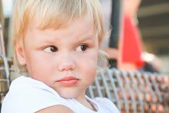Nahaufnahmeporträt im Freien des missfallenen netten Babys Stockbild