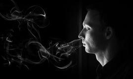 Nahaufnahmeprofilporträt des Mannes mit geschlossenen Augen und Rauche Stockfotografie