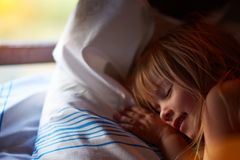 Nahaufnahmeprofilporträt des schönen blonden kaukasischen Mädchens mit geschlossenen Augen nahe einem Fenster mit weißen Vorhänge lizenzfreie stockfotos