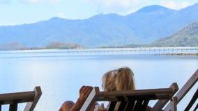 Nahaufnahmerückseiten-Ansichtmädchen sitzt im Strandstuhl macht selfie stock video footage