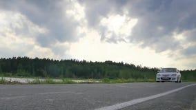 Nahaufnahmeradsport Die Szene hinten als die Sonne, die mit Windkraftanlagen in der Rückseite untergeht weißer Sportwagen auf der stock video