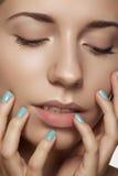 Nahaufnahmeschönheit. Vorbildliches Gesicht mit natürlichem Make-up u. heller Maniküre stockfoto