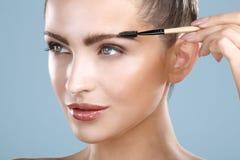 Nahaufnahmeschönheit mit Augenbrauenbürstenwerkzeug Stockfotos