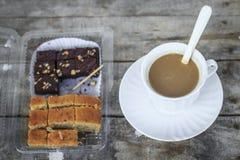 Nahaufnahmeschokoladenkuchen mit Kaffeetasse auf wei?em Hintergrund Lizenzfreie Stockfotografie