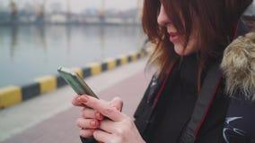 Nahaufnahmeschuß der Schönheit, die intelligenten Telefontechnologie App geht auf die Straße in einer warmen Jacke mit einer flau stock footage