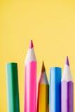 Nahaufnahmeschuß von den farbigen Bleistiften, die auf dem gelben Hintergrund stehen Lizenzfreies Stockfoto