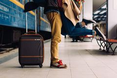 Nahaufnahmeschuß von den Frauenfüßen an stehend gehen bei der Umfassung ihres Mannes an der Bahnplattform für einen Abschied vor  Stockfoto