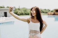 Nahaufnahmeselfieporträt des attraktiven Brunettemädchens mit dem langen Haar, das nahes Pool steht Sie trägt rosa T-Shirt, Sonne Stockbild