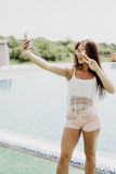 Nahaufnahmeselfieporträt des attraktiven Brunettemädchens mit dem langen Haar, das nahes Pool steht Sie trägt rosa T-Shirt, Sonne Lizenzfreies Stockbild