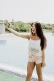 Nahaufnahmeselfieporträt des attraktiven Brunettemädchens mit dem langen Haar, das nahes Pool steht Sie trägt rosa T-Shirt, Sonne Lizenzfreie Stockfotografie