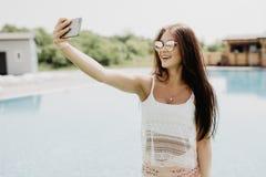 Nahaufnahmeselfieporträt des attraktiven Brunettemädchens mit dem langen Haar, das nahes Pool steht Sie trägt rosa T-Shirt, Sonne Stockfotografie
