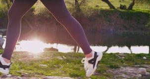 Nahaufnahmesonderkommandos einer laufenden Dame an der Natur durch die Rasenfläche bei Sonnenuntergang auf dem Hintergrund, Gesun