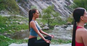 Nahaufnahmesonderkommandos von zwei Damen an der Natur, die dazu Yoga auf der Matte von überraschendem Fluss und von Berg, die si