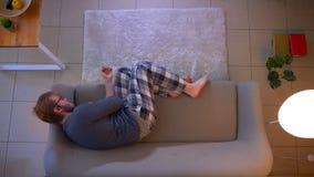Nahaufnahmespitzentrieb jungen zuf?llig gekleideten m?nnlichen aufpassenden Fernsehens, das zuhause auf der Couch ist deprimiert  stock video