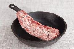 Nahaufnahmestück frisches gemarmortes Rindfleisch mit Seesalz und schwarzem Pfeffer, auf einer Gusseisengrillwanne Stockbild