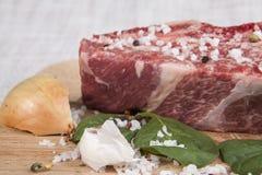 Nahaufnahmestück frisches gemarmortes Rindfleisch, Paprikapfeffer, Petersilie, Zwiebel, Knoblauch, Rippen liegen auf einem hölzer Stockfotografie