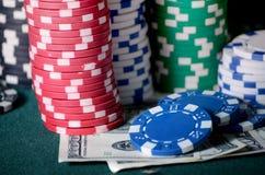 Nahaufnahmestapel Kasinochips und Dollarscheine auf der Pokertabelle Stockbilder