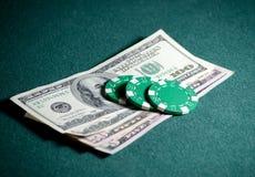 Nahaufnahmestapel Kasinochips und Dollarscheine auf der Pokertabelle Stockfoto