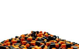 Nahaufnahmestapel von orange-schwarzen Kapselpillen auf weißem Hintergrund Vitamine und Erg?nzungen viele Flaschen Medizin global stockbilder
