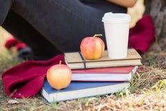 Nahaufnahmestudentenmädchen, das nahe bei Büchern, Kaffee und Apfel auf einem unscharfen Hintergrund sitzt Studieren des Konzepte stockfotografie