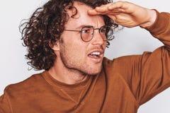 Nahaufnahmestudiobild des überraschten Mannes, der für Anzeige aufwirft, trägt die runden Gläser und weg schaut mit der Hand auf  lizenzfreie stockbilder