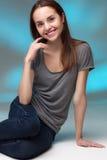 Nahaufnahmestudioporträt der jungen Frau im grauen Hemd Stockbild