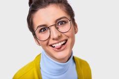Nahaufnahmestudioporträt der optimistischen lustigen Frau mit der Brötchenfrisur, die ihre Zunge zeigt und runde modische Schausp stockfoto