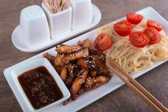 Nahaufnahmeteigwaren mit sauer-süßer Soße und zwei Essstäbchen Stockbild