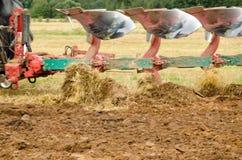 Nahaufnahmetraktorpflug, der landwirtschaftliches Feld pflügt stockbilder
