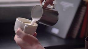 Nahaufnahmetrieb barista auslaufender Milch in einen dämpfenden Kaffee in einem Cup unter Verwendung des silbernen Werfers in ein stock video footage