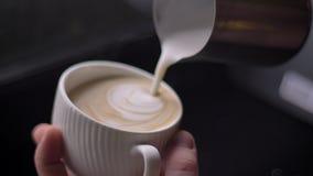 Nahaufnahmetrieb barista auslaufender Milch in einen dämpfenden Kaffee in einem Cup unter Verwendung des silbernen Werfers, der C stock footage