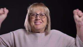 Nahaufnahmetrieb der älteren kaukasischen blonden Frau in den Gläsern, die aufgeregt erhalten und vor der Kamera mit feiern stock video footage