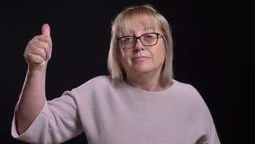 Nahaufnahmetrieb der alten kaukasischen blonden Frau in den Gläsern, die sich einen Daumen beim Kamera mit gerade betrachten zeig stock video