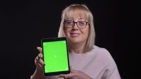 Nahaufnahmetrieb der alten kaukasischen blonden Frau in den Gläsern unter Verwendung der Tablette und des Zeigens des grünen Schi stock footage