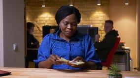 Nahaufnahmetrieb der erwachsenen Afroamerikanergeschäftsfrau, die das Bargeld glücklich zuhause lächelt im Büro zählt stock footage