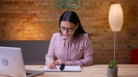 Nahaufnahmetrieb der erwachsenen asiatischen Geschäftsfrau, die auf dem Laptop nimmt die Kenntnisse betrachten Kamera und zuhause stock footage